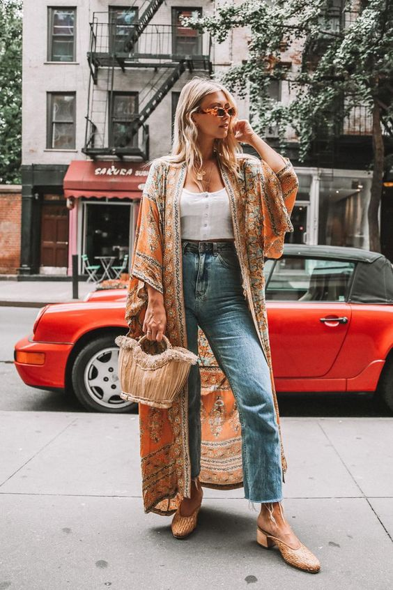 a white crop top, blue high waisted jeans, mules, a colorful printed kimono and a catchy neutral bag
