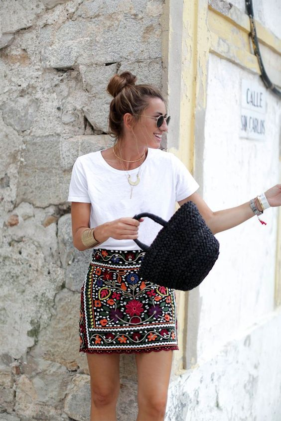 a white tee, a colorful floral mini skirt, a black straw bag and statement accessories