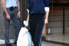 Victoria Beckham with a navy shirt, black side stripe pants, a white oversized bag