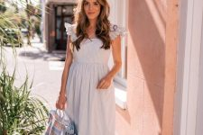 a blue and white vintage-inspired maxi dress with ruffle cap sleeves, a square neckline, a tote and espadrilles