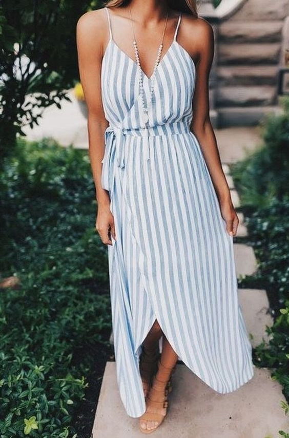 a blue and white wrap striped maxi dress with spaghetti straps, tan shoes and a pearl necklace