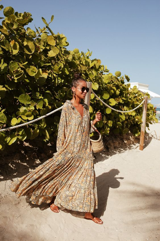 a boho oversized floral maxi dress with long sleeves, a wicker bag and brown slippers for a boho look