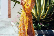 a bold sunny yellow printed maxi wrap dress with long sleeves, pompoms for a boho gypsy look