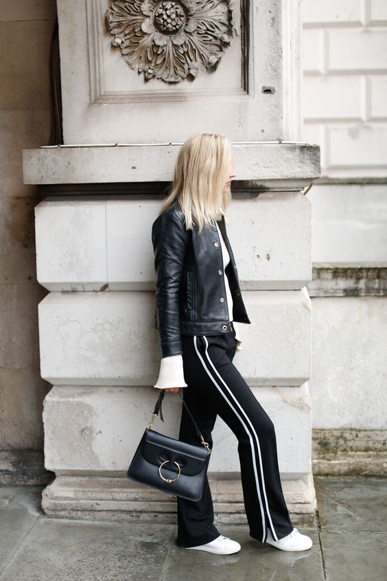 a casual outfit with a white top, black side stripe pants, white sneakers, a black bag