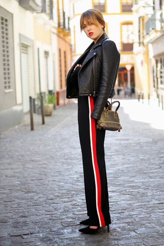 a chic look with black side stripe pants, a black leather jacket, black shoes and a brown leather bag