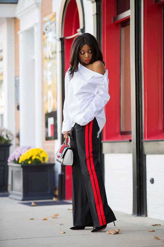 a chic outfit with a one shoulder white shirt, black side stripe pants, black heels and a striped bag