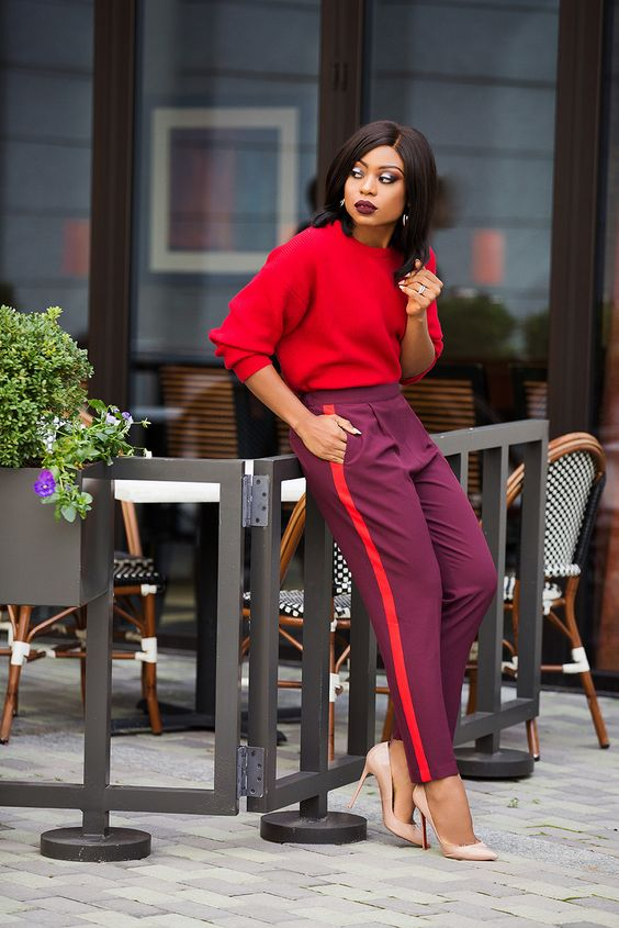 a colorful look with a hot pink sweatshirt, purple side stripe pants, nude heels