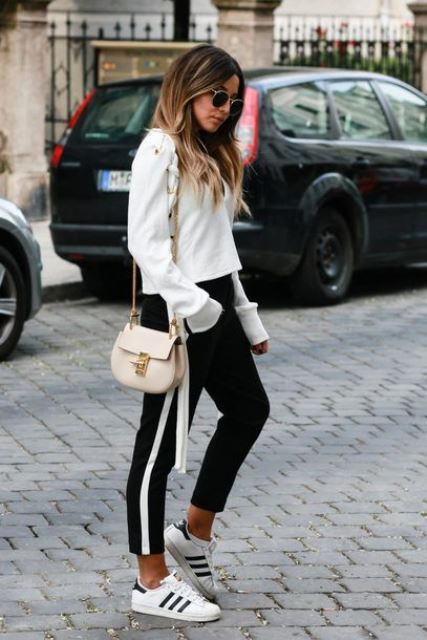 a contrasting look with a white sweatshirt, black side stripe pants, white sneakers and a neutral bag