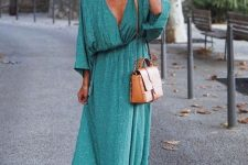 a green wrap printed maxi dress, layered necklaces, white sneakers, a brown bag and a black hat