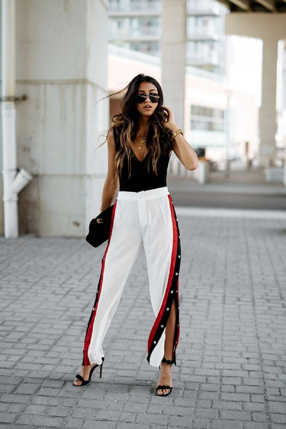 a party look with a black top, white side stripe pants, black shoes and a black bag