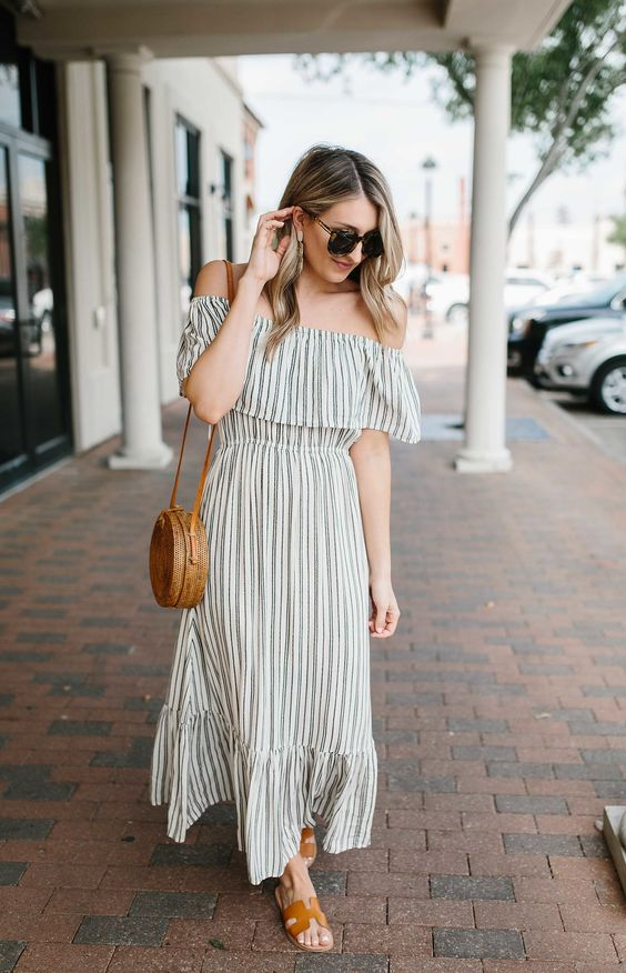 a simple striped off the shoulder A line maxi dress, brown leather slippers and a brown woven bag