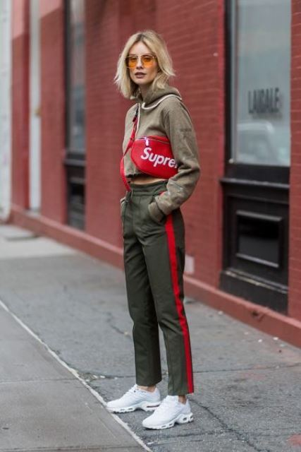a sport outfit with a green crop hoodie, green side stripe pants, white trainers and a red bag