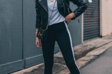 a stylish outfit with a white tee, black side stripe pants, a black leather jacket and black boots