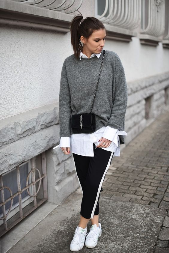 a stylish outfit with an oversized white shirt, a grey cashmere sweater, black side stripe pants, white sneakers and a crossbody bag