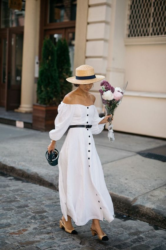 a white A-line maxi button up dress with long sleeves, two tone slingbacks and a hat for vintage look