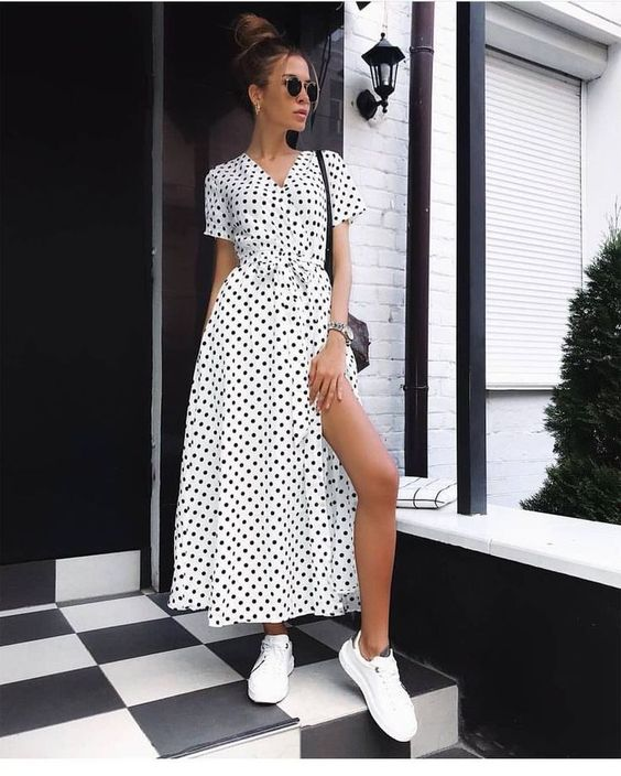 a white and black wrap polka dot maxi dress, white sneakers, a black bag for a monochromatic look