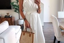 a white cotton A-line maxi dress with a high neckline and ruffle sleeves, brown slippers and a wicker bag