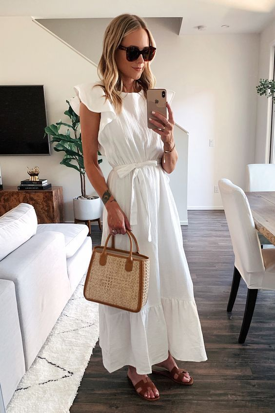 a white cotton A line maxi dress with a high neckline and ruffle sleeves, brown slippers and a wicker bag