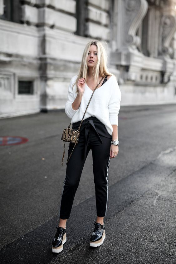 a white fluffy sweater, black side stripe pants, black star print Oxfords and a small snake skin bag