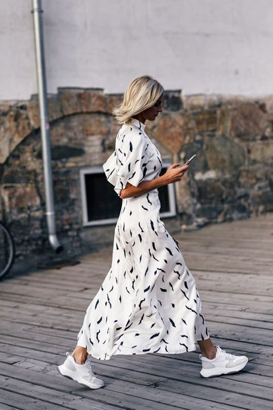 a white printed maxi A-line dress with short sleeves and white trainers for a chic look