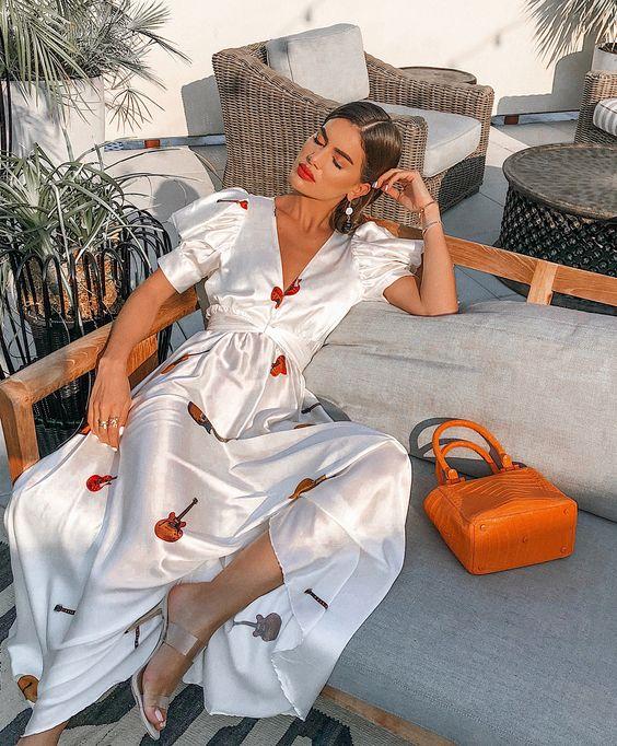 a white silk A-line maxi dress with a fun print, short sleeves, tan heels and an orange bag