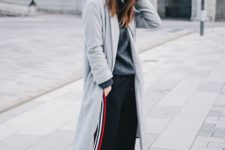 a winter outfit with a grey sweater, black side stripe pants, white sneakers, a grey beanie and a grey coat