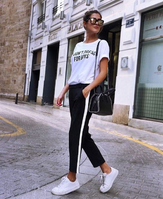 an everyday look with a white printed tee, black side stripe pants, white sneakers, a black bag