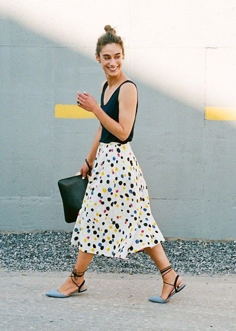 a bright summer work outfit with a black top, a colorful polka dot midi, blue lace up flats and a clutch