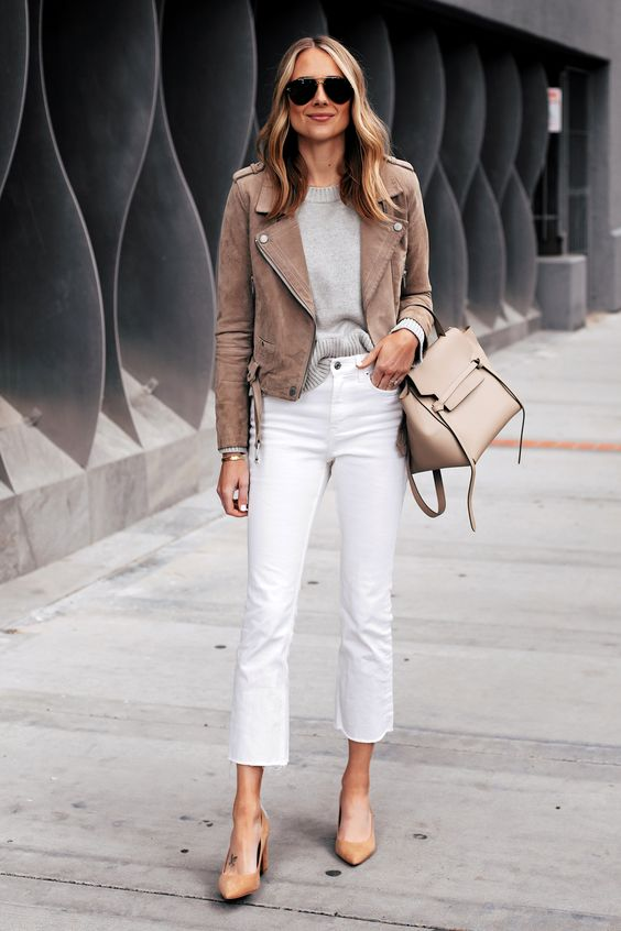a grey top, white cropped jeans, neutral shoes, a brown cropped suede jacket and a neutral bag