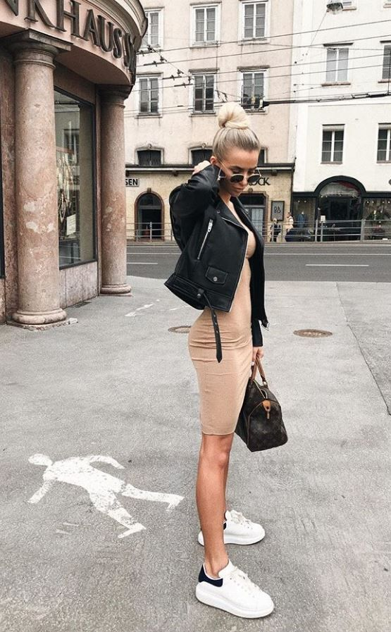 a tan bodycon over the knee dress, a black leather jacket, white sneakers and a brown bag