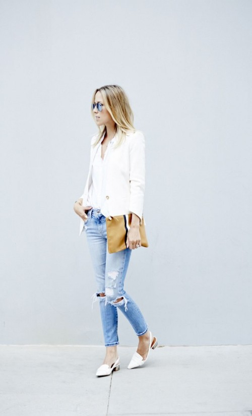 a spring outfit with blue ripped jeans, a white top and blazer, white kitten heel shoes and a brown clutch