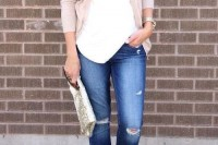 navy ripped jeans, a white top, a tan cardigan, white flats and a metallic clutch for a spring feel
