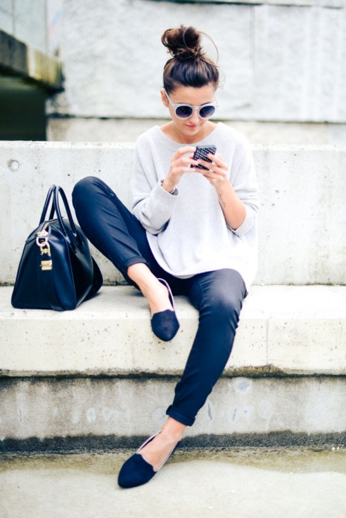 a monochromatic outfit with black skinny pants, an oversized grey top, black flats and a black bag