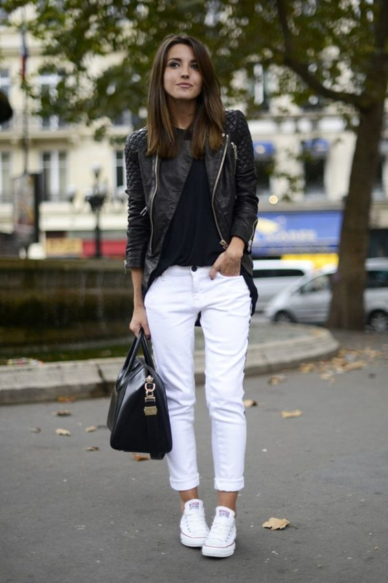 white jeans and sneakers, a black top, a black leather jacket and a black bag