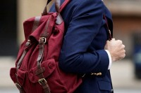 a burgundy fabric backpack is a nice colorful ottouch to most of your outfits