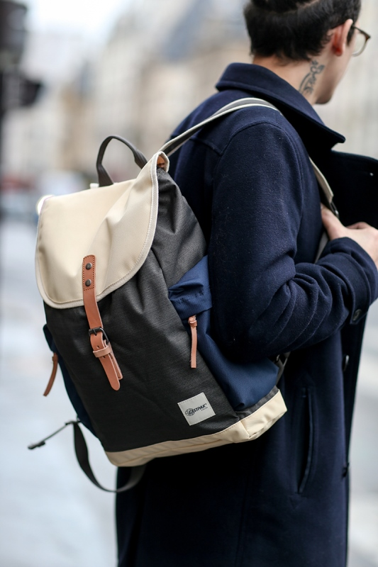 a stylish color block backpack in cream, navy and black and with faux brown leather detailing