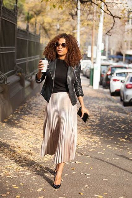 a black top, a blush pleated misi skirt, a black leather jacket and black shoes and a clutch