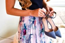 a black top, a floral pleated knee skirt, blue ankle strap shoes for a simple and cute work outfit in spring