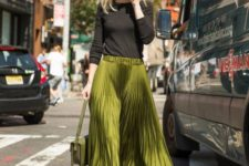 a black top, a green pleated midi skirt, a matching bag and black shoes for a spring work look