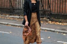 a blakc top, a black oversized blazer, an animal print midi skirt, white sneakers and a brown bag