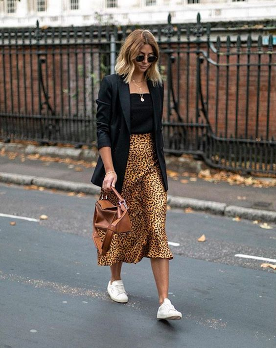a blakc top, a black oversized blazer, an animal print midi skirt, white sneakers and a brown bag