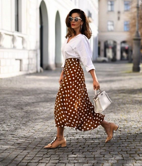 a chic look with an oversized white shirt, a chic brown polka dot midi skirt, nude embellished shoes and a white bag