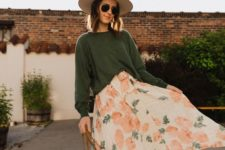 a green oversized top, a bright floral print midi skirt, white sneakers, a bucket bag and a hat