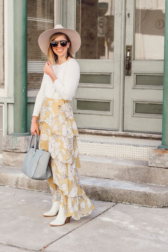 a statement print outfit with a white top, a yellow floral layered maxi skirt, white cowboy boots, a grey tote and a hat