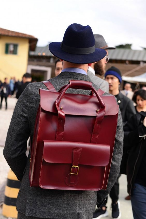 a super bold burgundy leather backpack with a top handles for carrying it as a bed