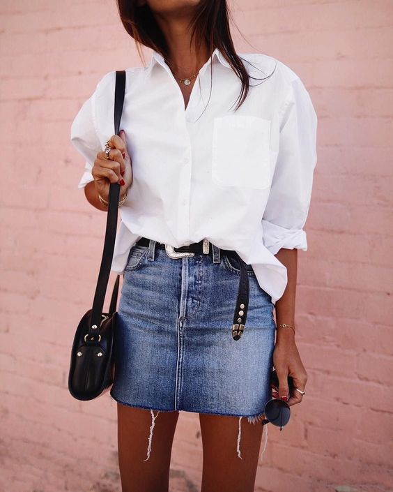 a white oversized shirt, a blue denim mini, a black crossbody bag and a black belt to match