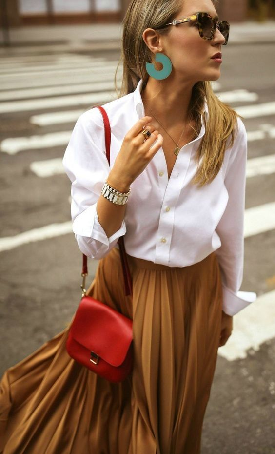 a white oversized shirt, a mustard pleated midi skirt, a red crossbody and statement earrings