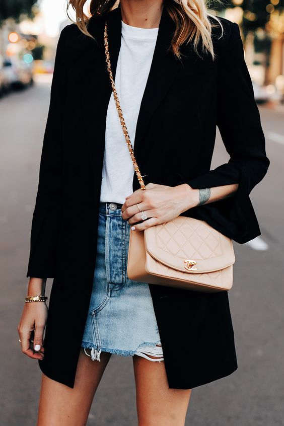 a white tee, a blue ripped mini skirt, a black long blazer and a neutral bag compose a sexy look