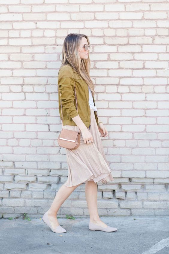 a white tee, a blush pelated skirt, nude flats, a pink bag and a mustard-colored bomber jacket