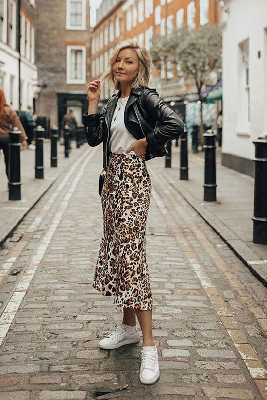 a white tee, an animal print midi skirt, a black leather jacket, white sneakers and a crossbody